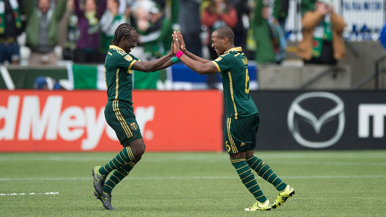 Portland Timbers midfielder Diego Chara, left, celebrates with teammate Darlington Nagbe, right, after Nagbe scored a goal in a game against the Colorado Rapids during the first half of their match in Portland Sun., Oct. 25, 2015. (AP Photo/Troy Wayrynen)