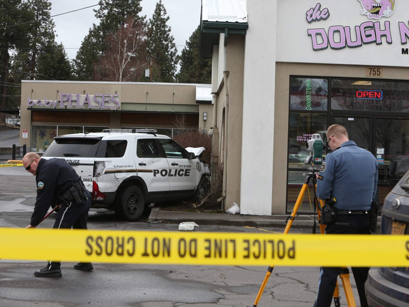 Officers work on the scene of an accident where a Bend PD SUV struck the Dough Nut Midtown shop at NE Eighth St. and Greenwood Ave. early Saturday. The officer driving the SUV was responding to a call, according to Bend Police. (Andy Tullis, The Bulletin)