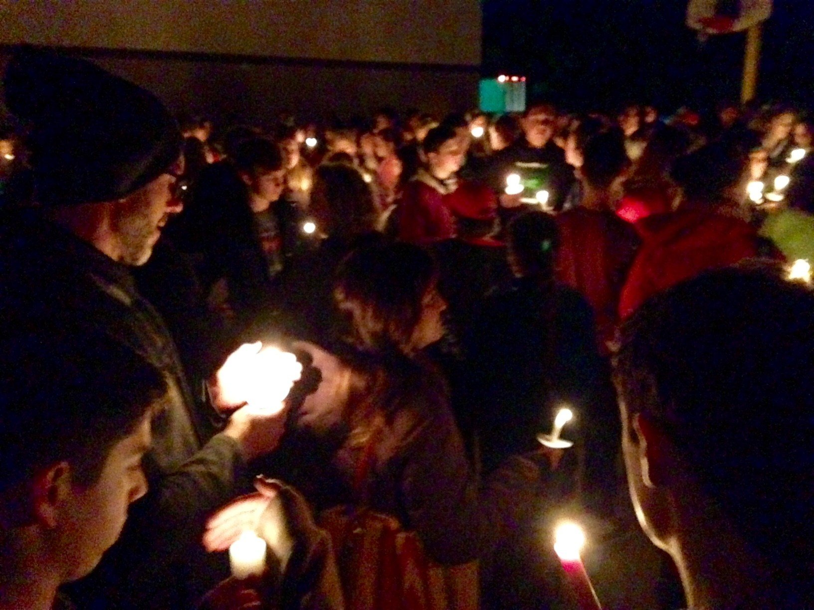 People holding candles at a vigil Monday to honor Doug Bonham and Matthew Albrecht.