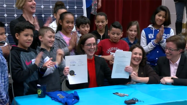 Governor Kate Brown signed OR SB 1547 banning coal-use for energy at James John Elementary Friday. (PPS Communications)