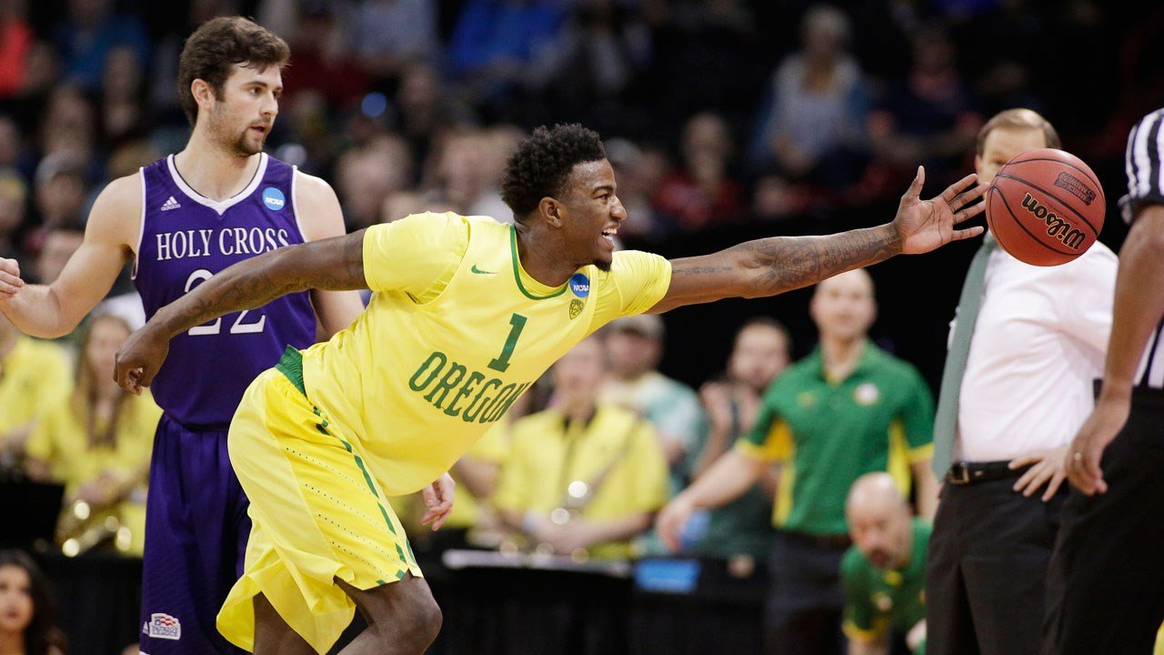 Oregon fwd Jordan Bell goes after a loose ball in front of Holy Cross gd Robert Champion during the first half of a first-round men's college basketball game in the NCAA Tournament in Spokane, Wash., Friday, March 18, 2016. (AP Photo/Young Kwak)