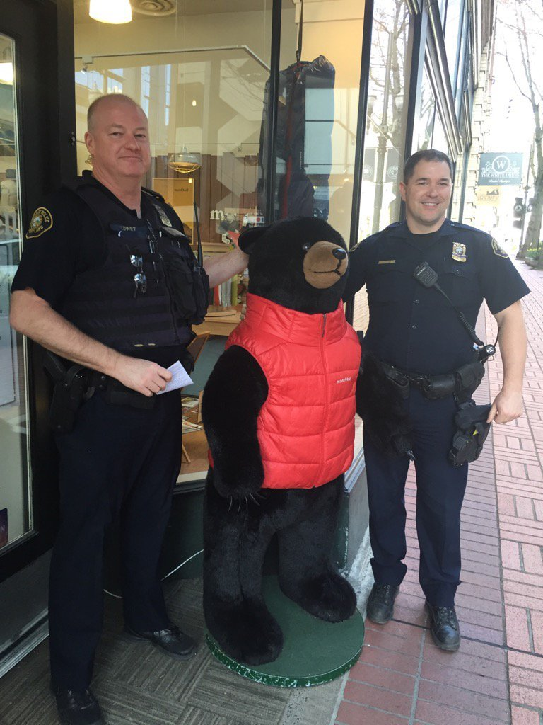 PPB officers pose with the bear outside of the Montbell store in downtown Portland after returning the mascot's jacket, which was stolen earlier in the week. (Kandra Kent/KPTV)