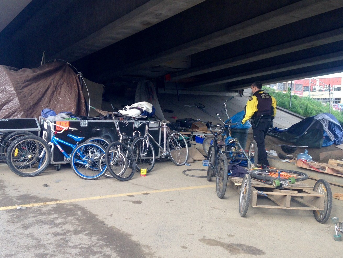"Officers talking with people at a known ""chop shop"" under an east-side overpass."
