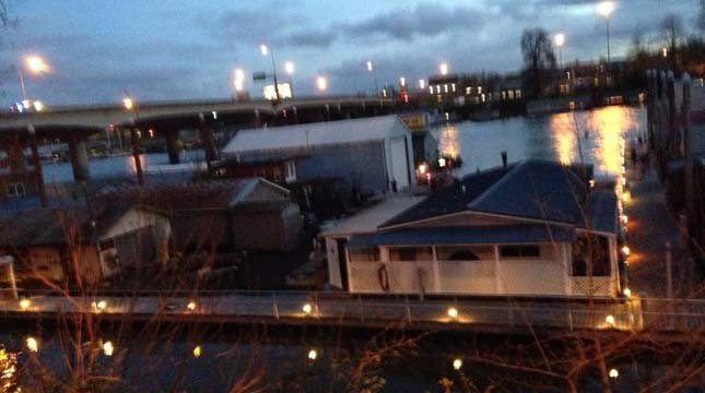 A wanted man was arrested after jumping into the Columbia River and then climbing on a dock of floating homes.