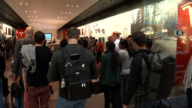 People waited in line at the Washington Square mall Thursday, hoping to be among the first to sign up for a new Tesla.