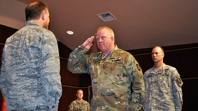 Brig. Gen. Todd Plimpton gives a final salute to Maj. Gen. Michael Stencel as he relinquishes command of the Oregon Army National Guard (Land Component) to Brig. Gen. William Edwards (right) in a ceremony April 3. (Oregon Military Department)