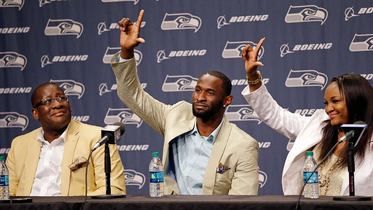 """Seattle Seahawks' Ricardo Lockette motions with an """"L,"""" representing """"love our brothers"""" as his mother Felita follows his lead and his father Earl looks on at a news conference announcing his retirement from football. (AP Photo/Elaine Thompson)"""