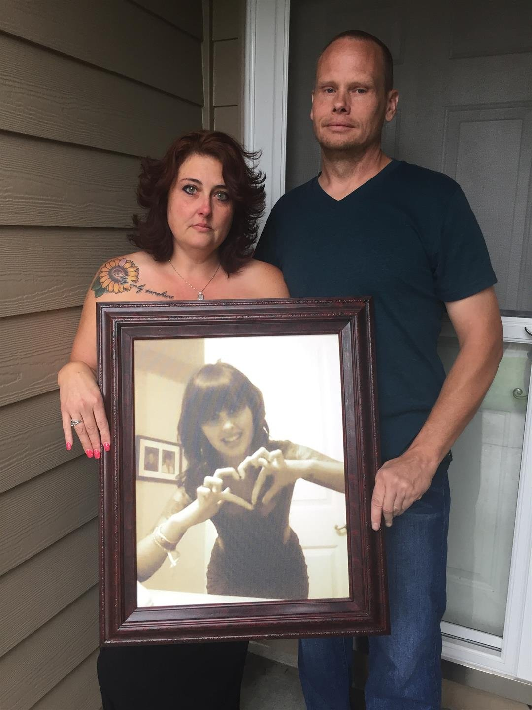 Stephanie and Doug Stolzenberger hold a photo of their daughter Cassandra