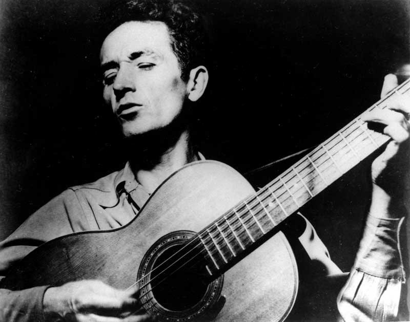This is an undated photograph of folk singer Woody Guthrie, singing a song and playing his guitar. Guthrie has written hundreds of songs, celebrating migrant workers, pacifists, and underdogs. (Source: AP)