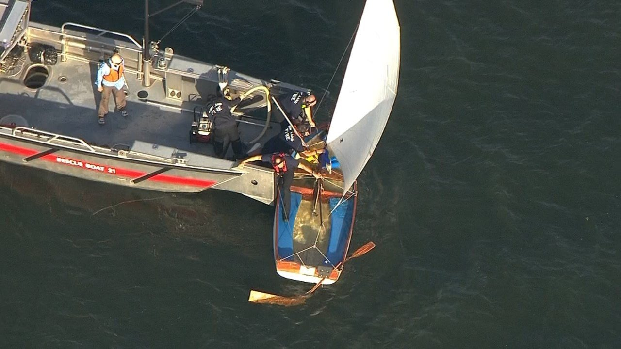 PFandR boat crew pumping water out of the capsized sailboat. (KPTV)
