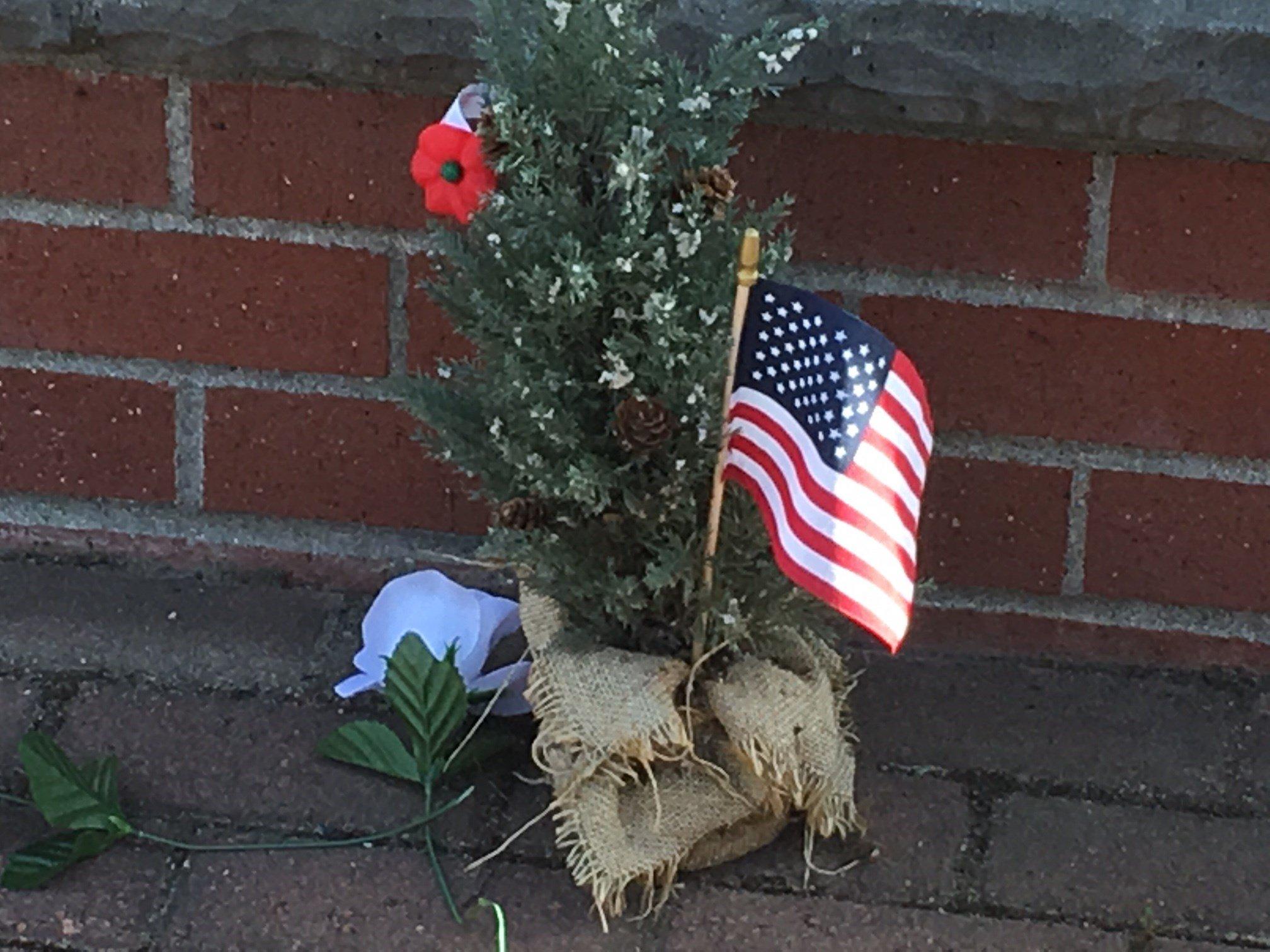 Flowers and an American flag sit at the Gresham Heroes Memorial. (KPTV)