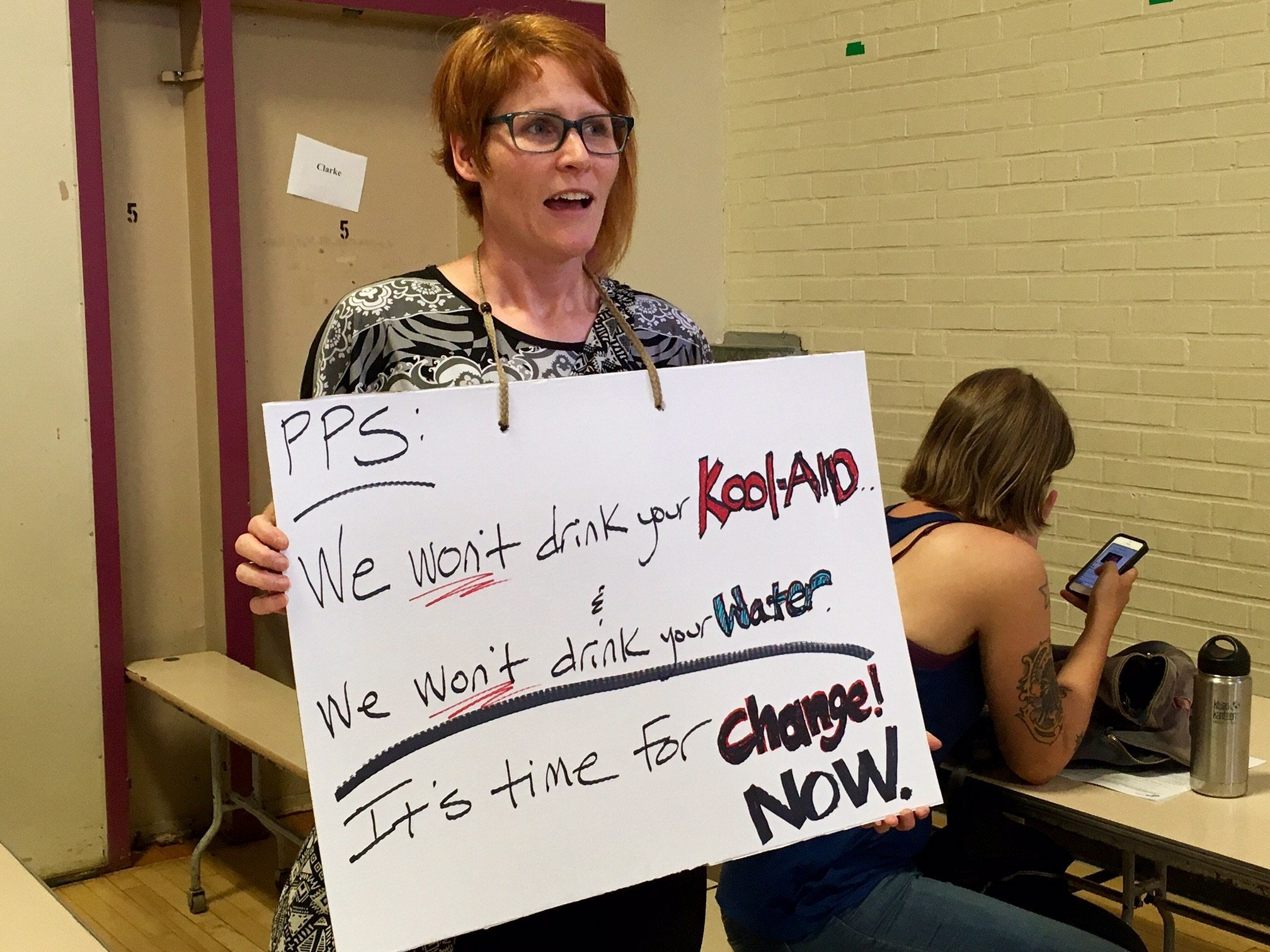 A woman holding a sign at Wednesday's meeting. (KPTV)