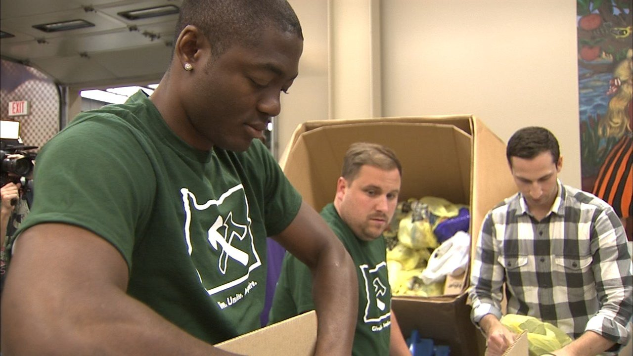 Timbers forward Fanendo Adi worked with other volunteers filling boxes at the Oregon Food Bank Thursday as part of Stand Together Week. (KPTV)