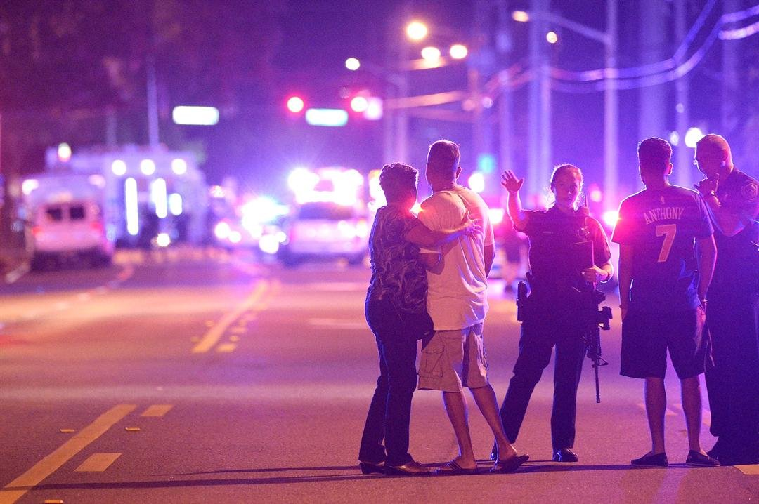 Orlando Police officers direct family members away from a fatal shooting at Pulse Orlando nightclub in Orlando, Fla., Sunday, June 12, 2016. (AP Photo/Phelan M. Ebenhack)