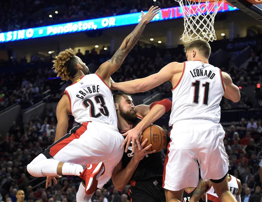 Toronto Raptors center Jonas Valanciunas (17) drives to the basket on Portland Trail Blazers guard Allen Crabbe (23) and forward Meyers Leonard (11) during the second half of an NBA basketball game in Portland, Ore., (AP Photo/Steve Dykes)