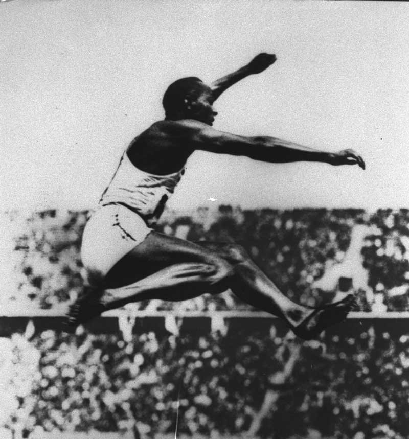 Track and field champion Jesse Owens is shown earning one of his four gold medals at the 1936 Berlin Summer Olympics, where he set an Olympic broad jump record of 26 feet, 5 1/2 inches, which remained unbroken for 24 years. (AP Photo)