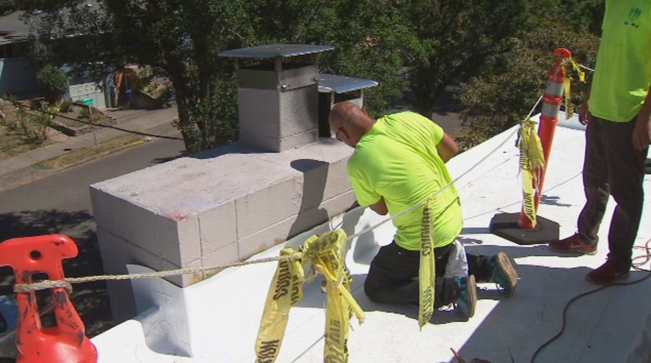 Roofing crews at work in SE Portland Wednesday. (KPTV)