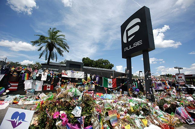 This photo taken July 11, 2016, shows a makeshift memorial continuing to grow outside the Pulse nightclub, the day before the one month anniversary of a mass shooting, in Orlando, Fla.  (AP Photo/John Raoux)