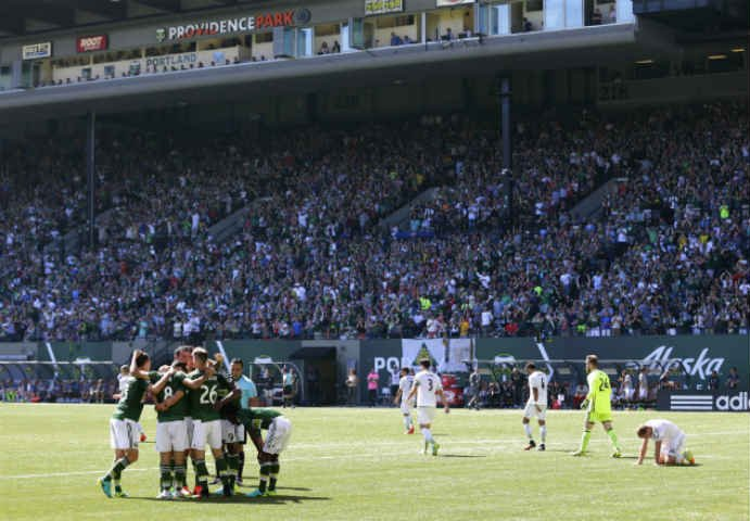 Timbers players congratulate Timbers forward Lucas Melano after Melano scored the the third of four team goals for the Timbers in the first half of an MLS soccer match against the Seattle Sounders, Aug. 28, in Portland, Ore. (AP Photo/Ted S. Warren)