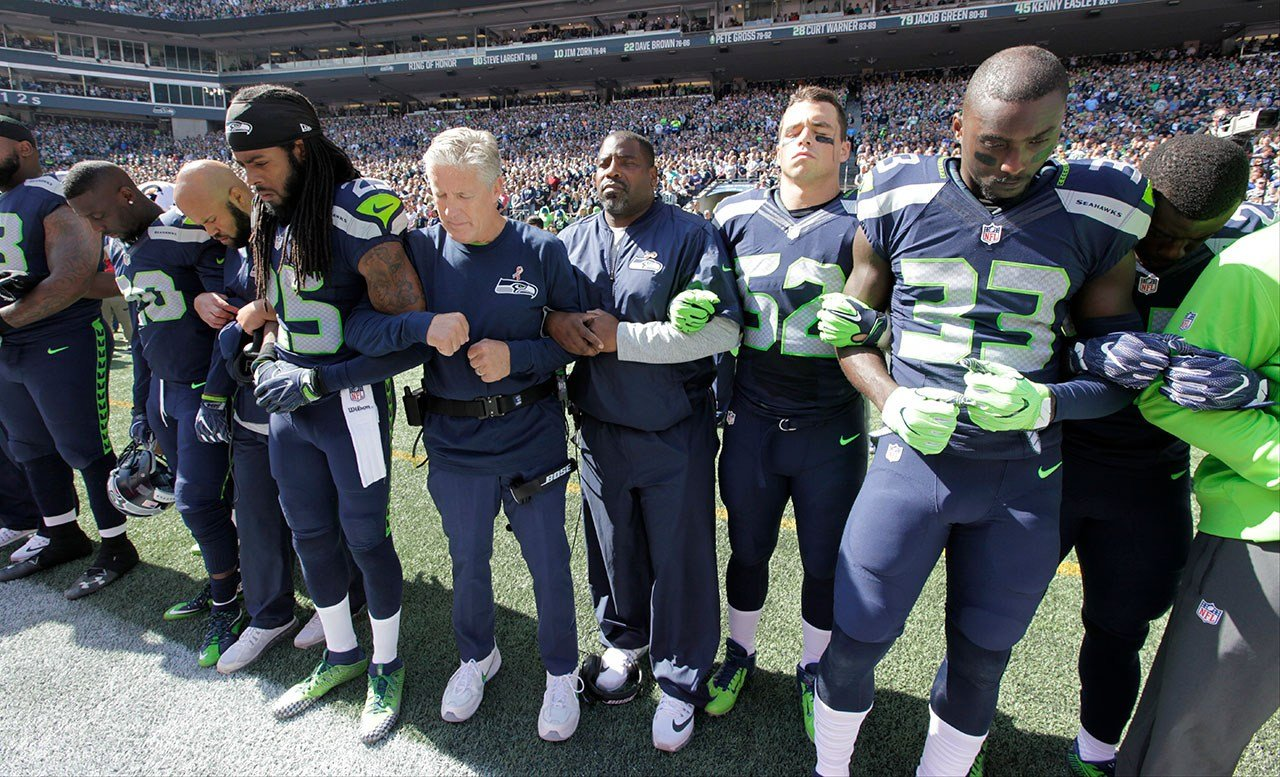 Seattle Seahawks players and coaches, including head coach Pete Carroll, center left, stand and link arms during the singing of the national anthem before an NFL football game against the Miami Dolphins Sunday in Seattle. (AP/Elaine Thompson)