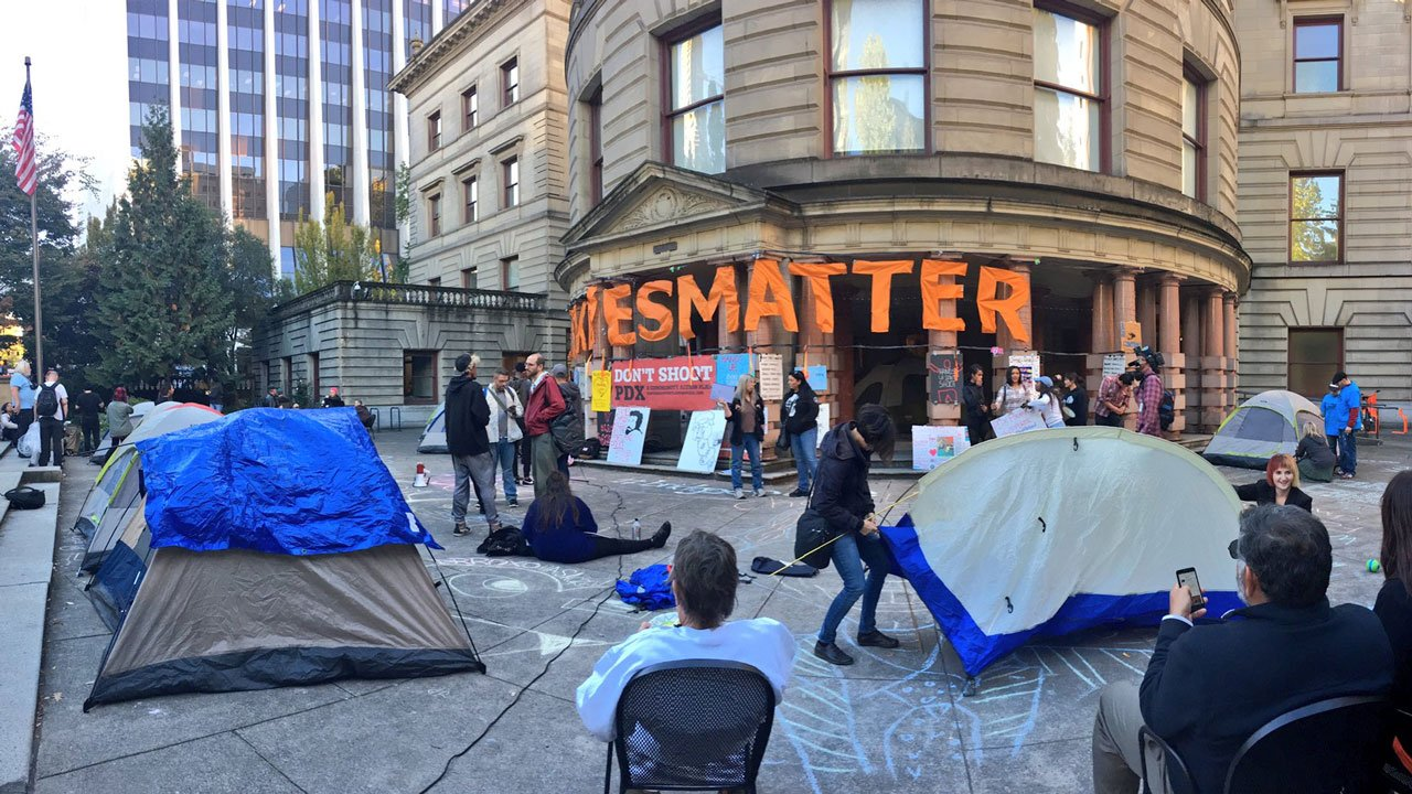 Demonstrators gathered outside of Portland City Hall Tuesday night to camp out before a planned vote on a new police contract by the city council Wednesday. (KPTV)