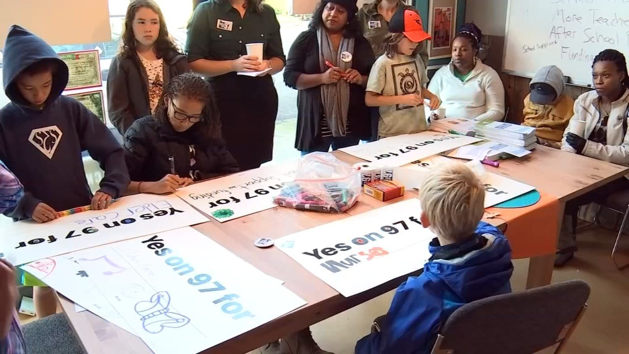 Parents and students from Portland Public Schools creating lawn signs supporting Measure 97. (KPTV)
