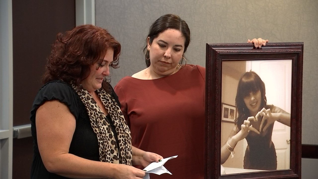 Family members holding a photo of Cassandra Stolzenberger while addressing the man who caused the crash that killed her in Aloha in September 2015. (KPTV)