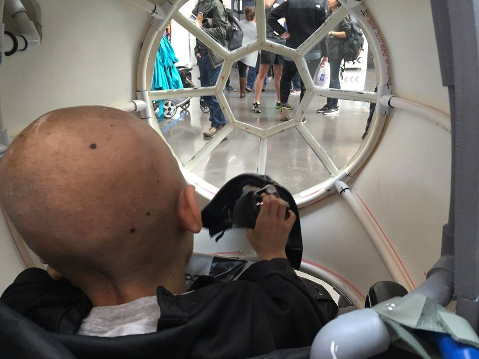 Daniel, a young patient fighting brain and spinal cancer, surveyed the crowd gather today for the unveiling of the latest Magic Wheelchair through the cockpit of his new TIE Fighter. (KPTV)
