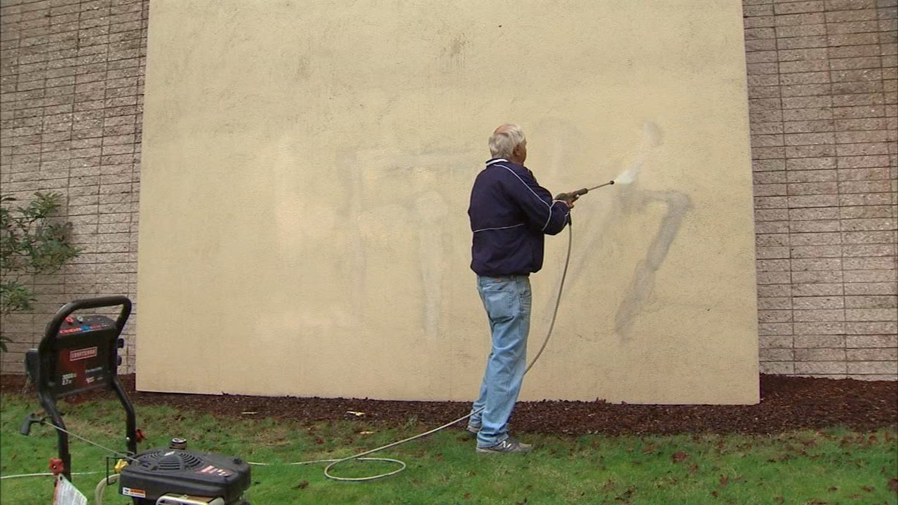 Racist graffiti being cleaned from a wall at Trinity Lutheran Church in Longview. (KPTV)