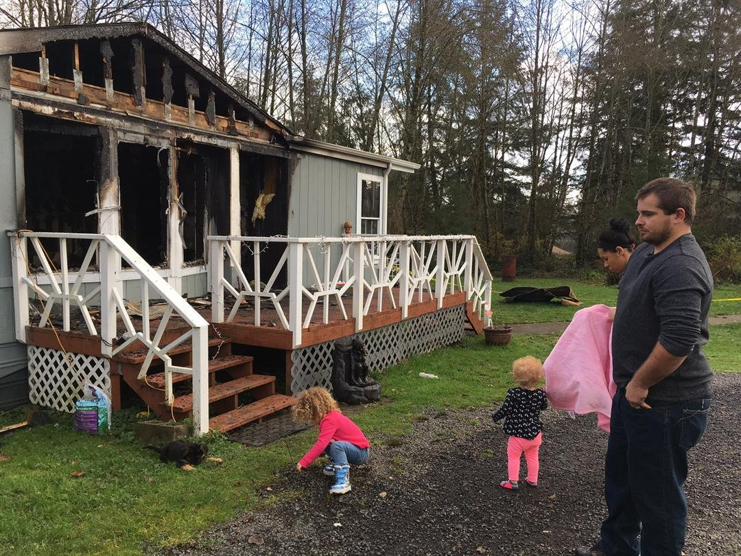 The Lovato's in front of their burned home in Longview Tuesday. (KPTV)