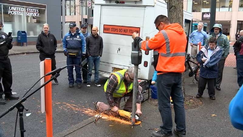 City workers used an electric saw to remove the meter and its post from a sidewalk on Southwest Pine Street.