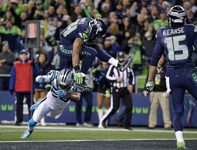 Seattle Seahawks' Thomas Rawls (34) leaps over Carolina Panthers' Daryl Worley to score a touchdown in the first half of an NFL football game, Sunday, Dec. 4, 2016, in Seattle. (AP Photo/Ted S. Warren)
