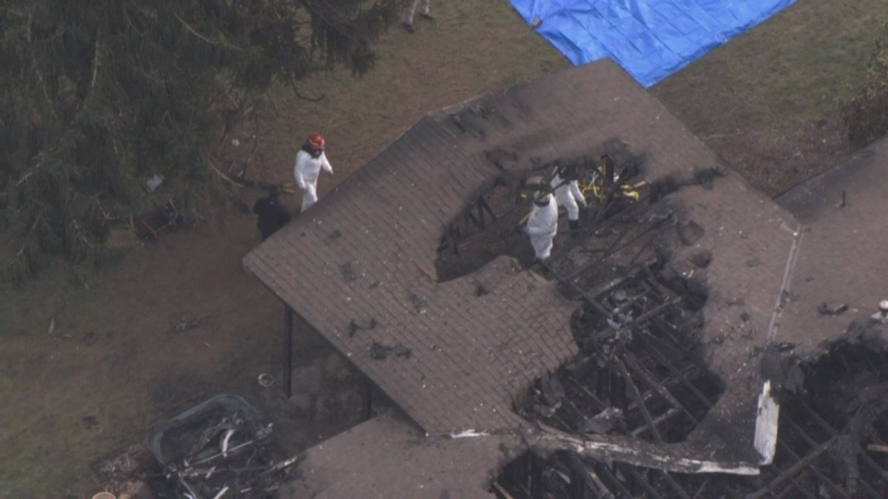 Investigators at the scene in Hubbard where five bodies were found in a burned home. (KPTV)