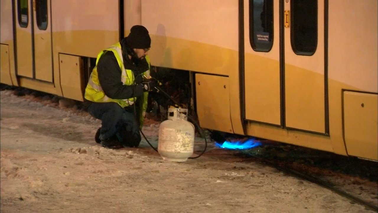 TriMet crews used shovels and blowtorches in efforts to clear the ice that caused a MAX train derailment Friday morning. (KPTV)