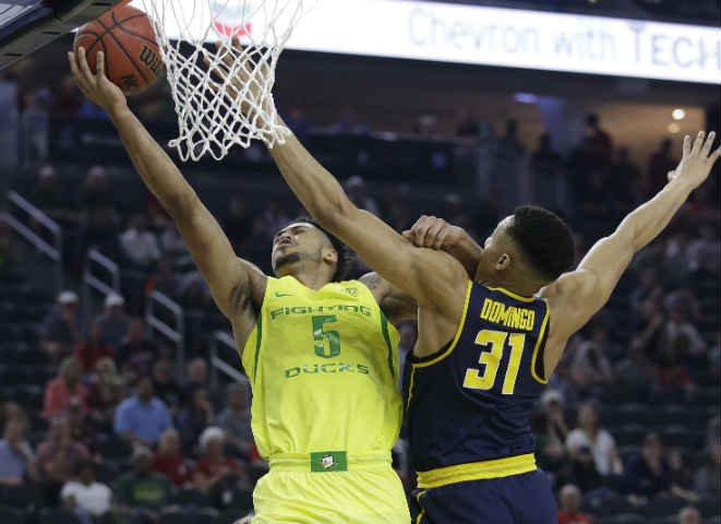 Oregon's Tyler Dorsey shoots around California's Stephen Domingo during the first half of an NCAA college basketball game in the semifinals of the Pac-12 tournament in Las Vegas. (AP Photo/John Locher)