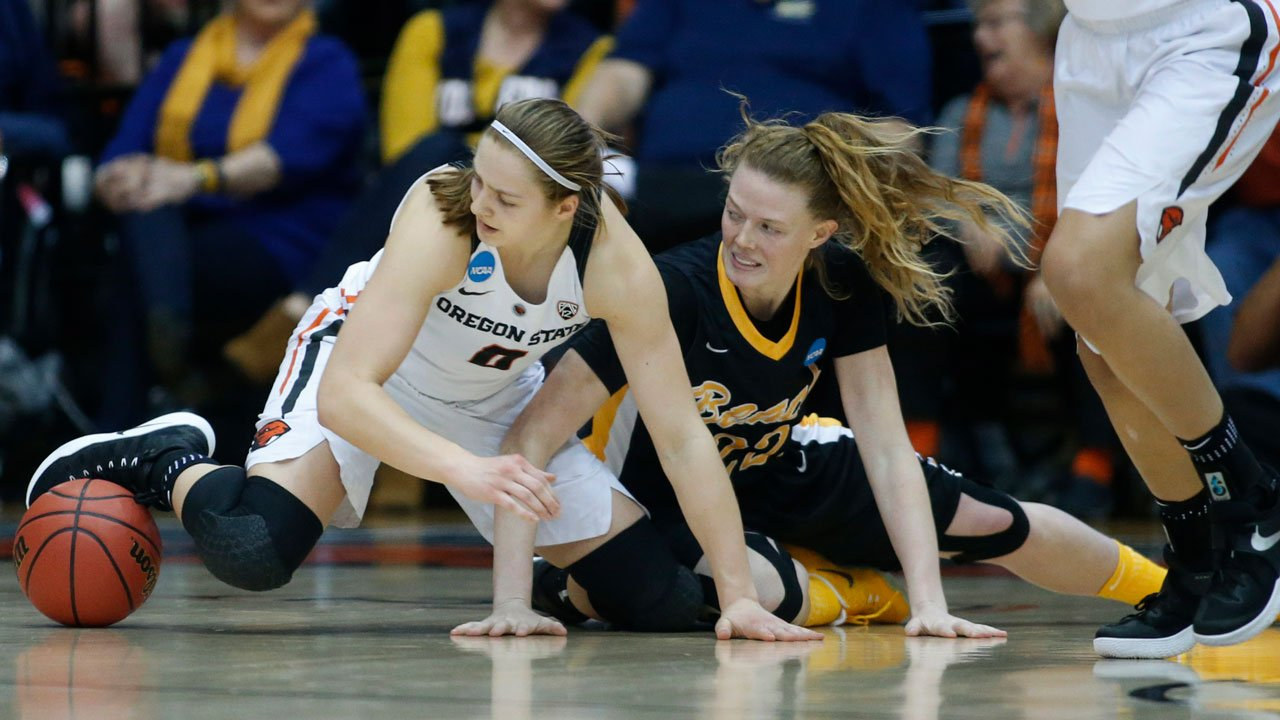 Oregon State's Mikayla Pivec and Long Beach State's Madison Montgomery hit the floor chasing a loose ball during the second half of a first-round game in the women's college basketball tournament Friday in Corvallis, Ore. (AP Photo/ Timothy J. Gonzalez)