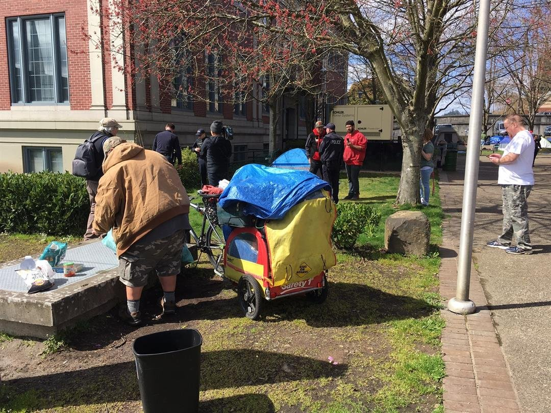 People packing up their tents outside Cowlitz County's administration building in Kelso Friday.