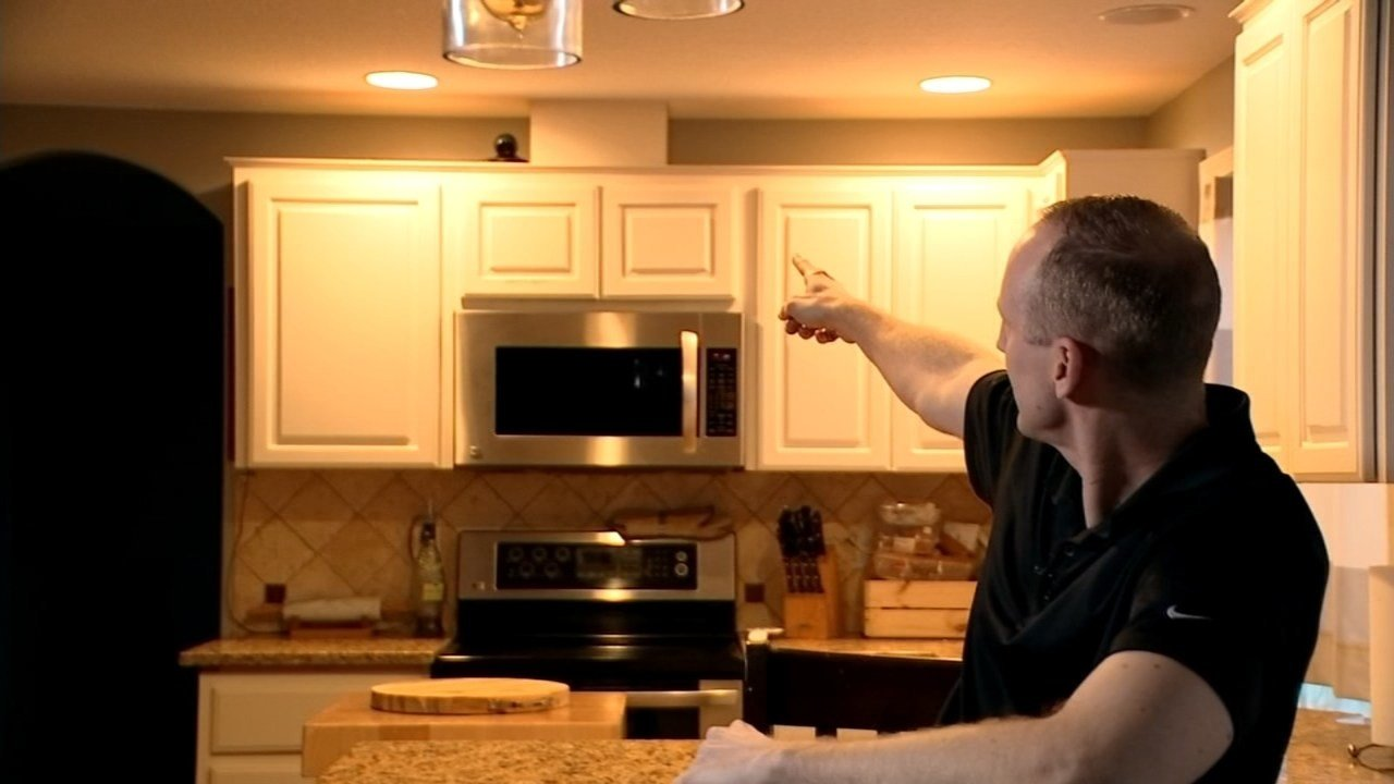 Travis Clarke pointing to a surveillance camera that captured a real estate agent, who is now a burglary suspect, in his home. (KPTV)