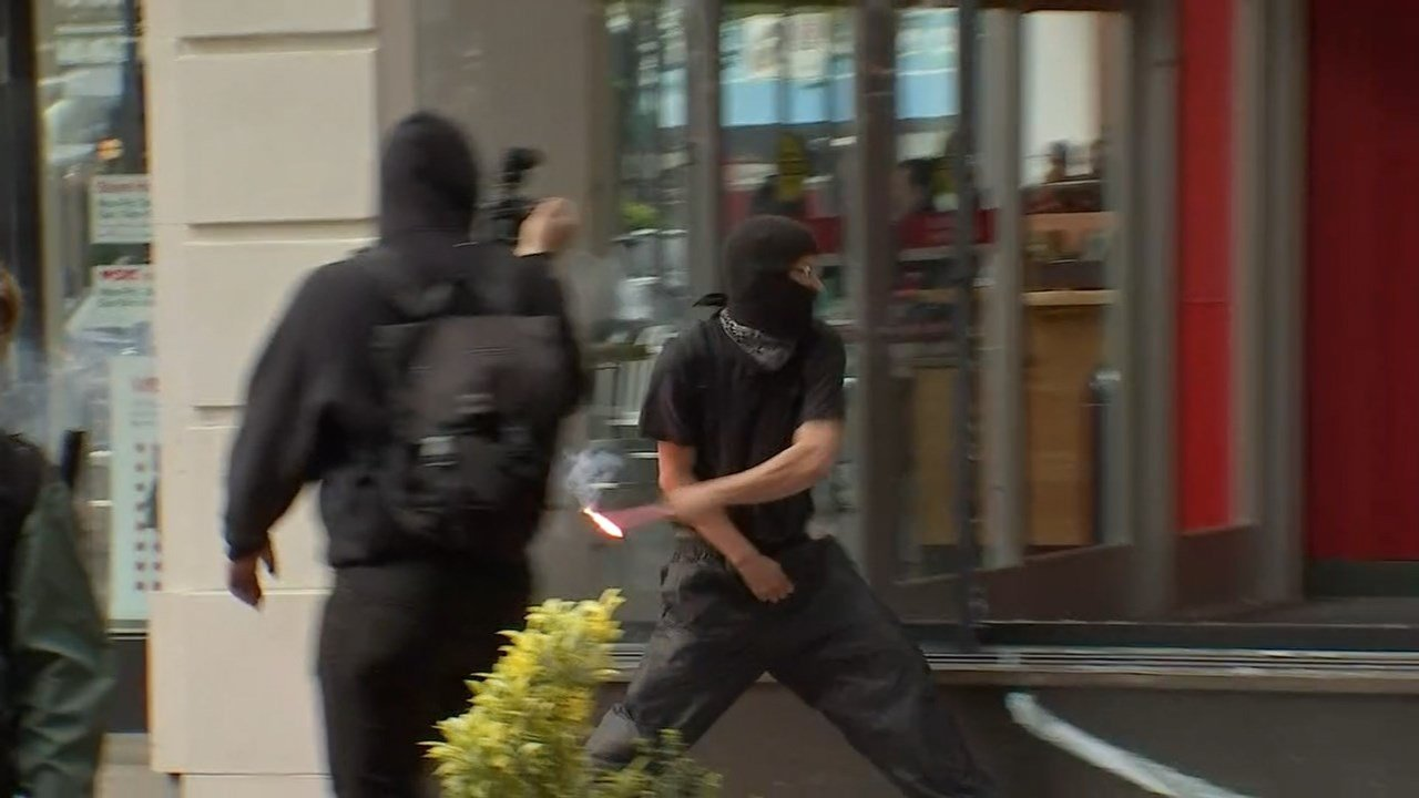 Image of protester throwing a lit flare into a Target store in downtown Portland on Monday. (KPTV)