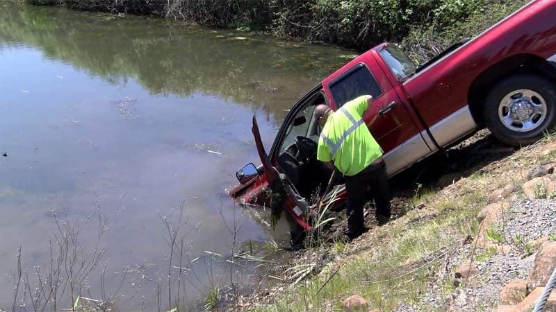 A truck crashed into a pond near the Stayton Pharmacy on Monday. (KPTV)