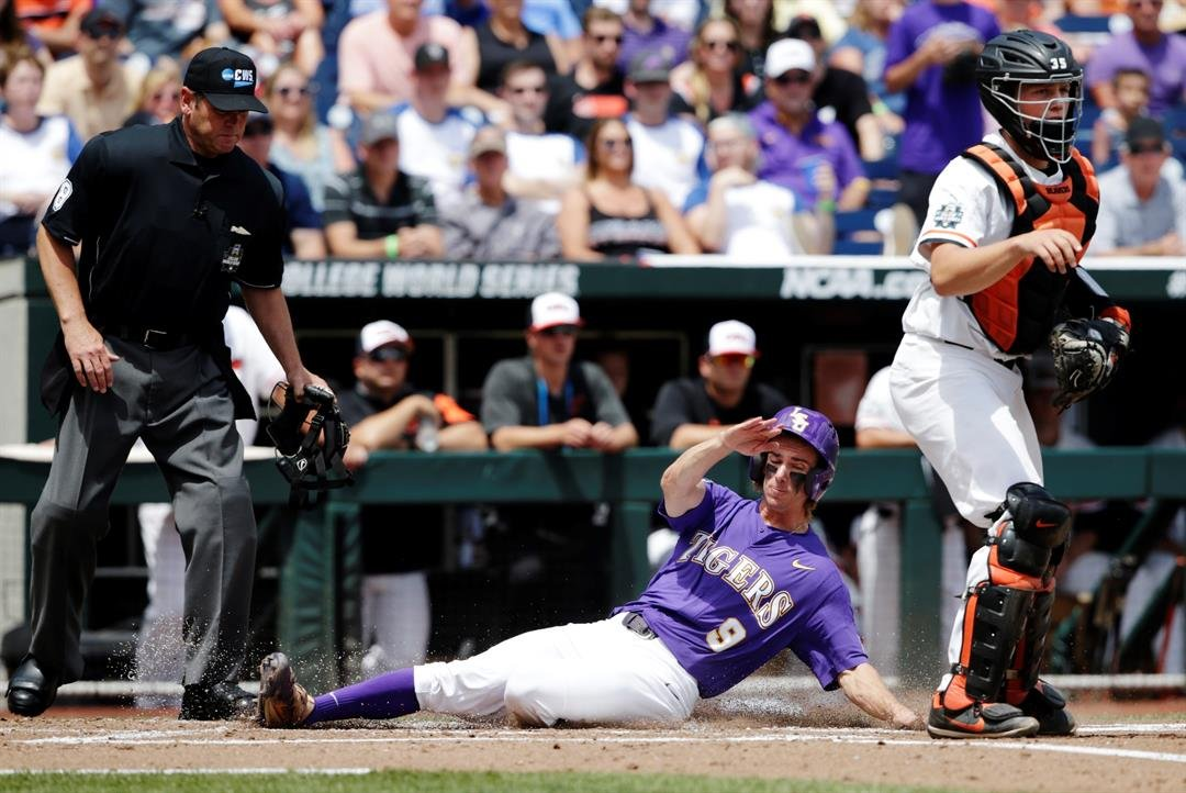 LSU's Zach Watson (9) slides past Oregon's catcher Adley Rutschman (35) to score on a sacrifice bunt by Beau Jordan during the second inning of an NCAA College World Series baseball game in Omaha, Neb., Friday, June 23, 2017. (AP Photo/Nati Harnik)