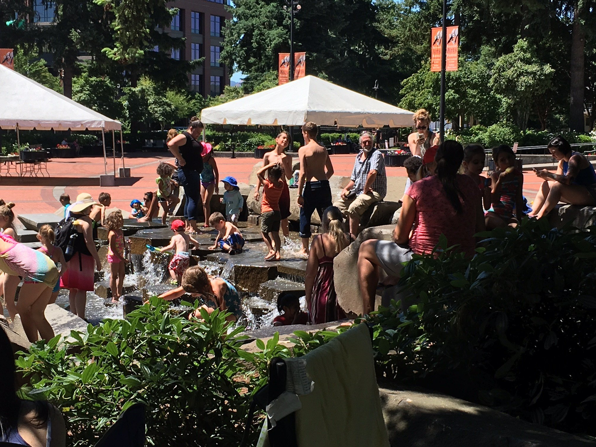 People cooling off in the fountain at Vancouver's Esther Short Park Friday.