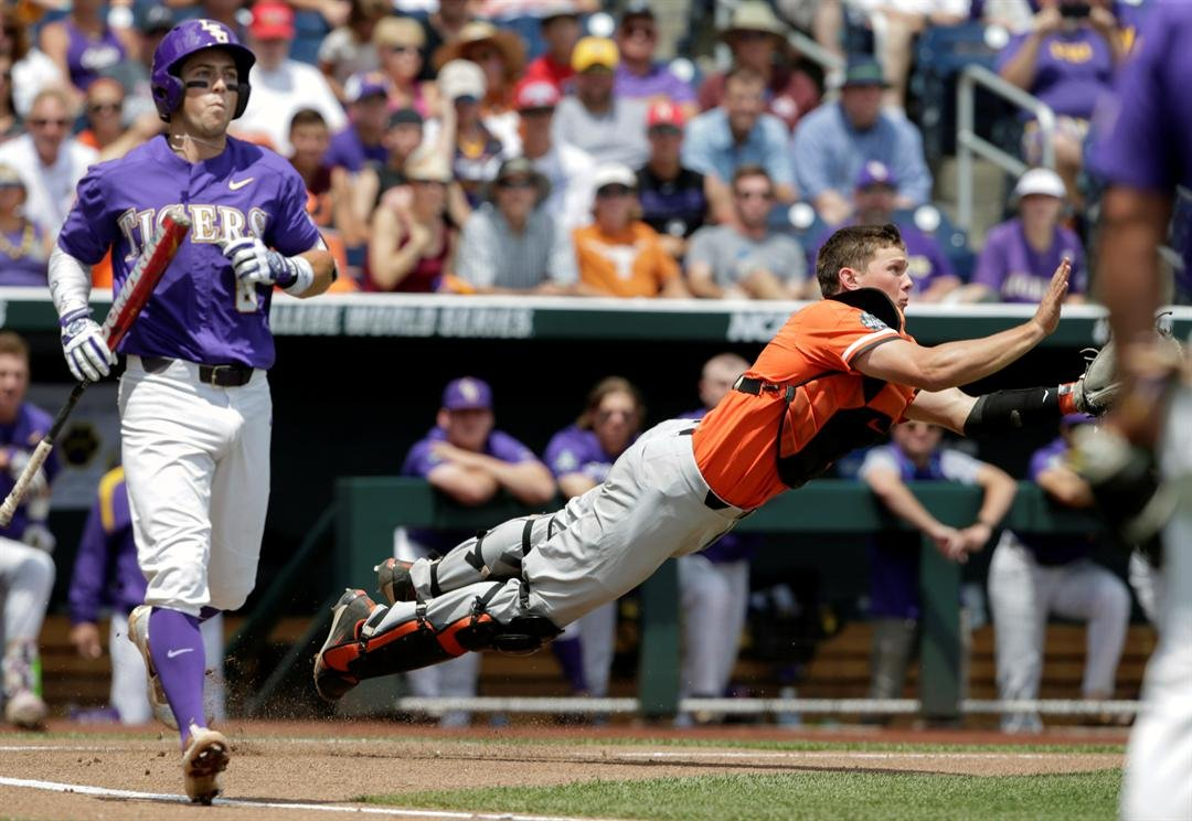 Oregon State catcher Adley Rutschman leaps to catch a foul ball hit by LSU's Cole Freeman (8) for an out in the first inning of an NCAA College World Series baseball elimination game in Omaha, Neb., Saturday, June 24, 2017. (AP Photo/Nati Harnik)