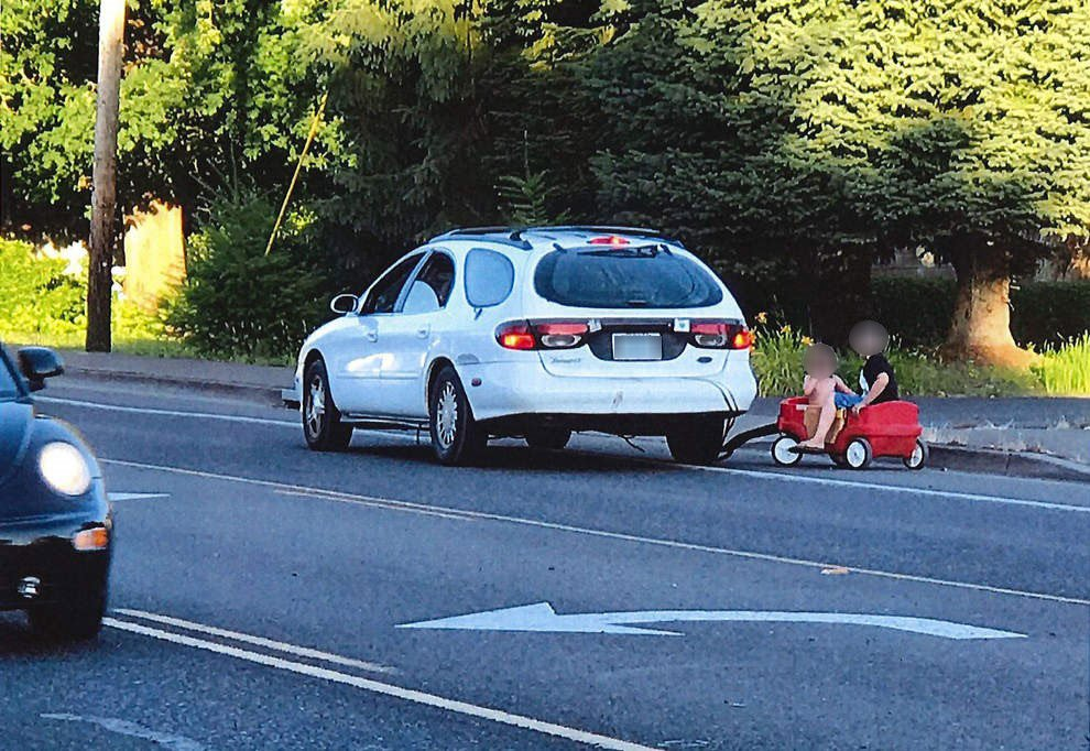 Oregon Woman Arrested for Towing Kids in Little Red Wagon Behind Car class=