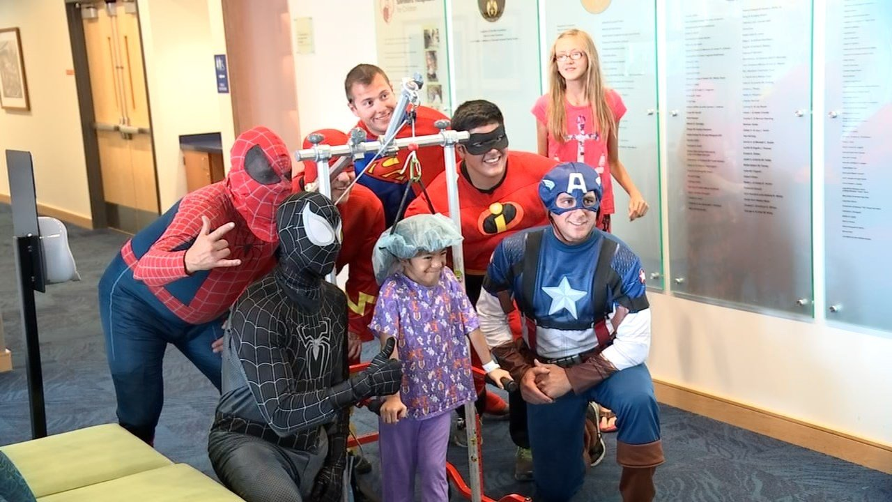 Superheroes surprise kids by washing windows at Shriners Hospital in Portland
