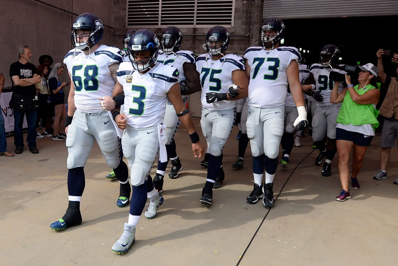 Seattle Seahawks QB Russell Wilson & C Justin Britt walk to the field with arms linked after the national anthem had been played before the game between the Seahawks and the Tennessee Titans Sept. 24, 2017, in Nashville. (AP Photo/Mark Zaleski)