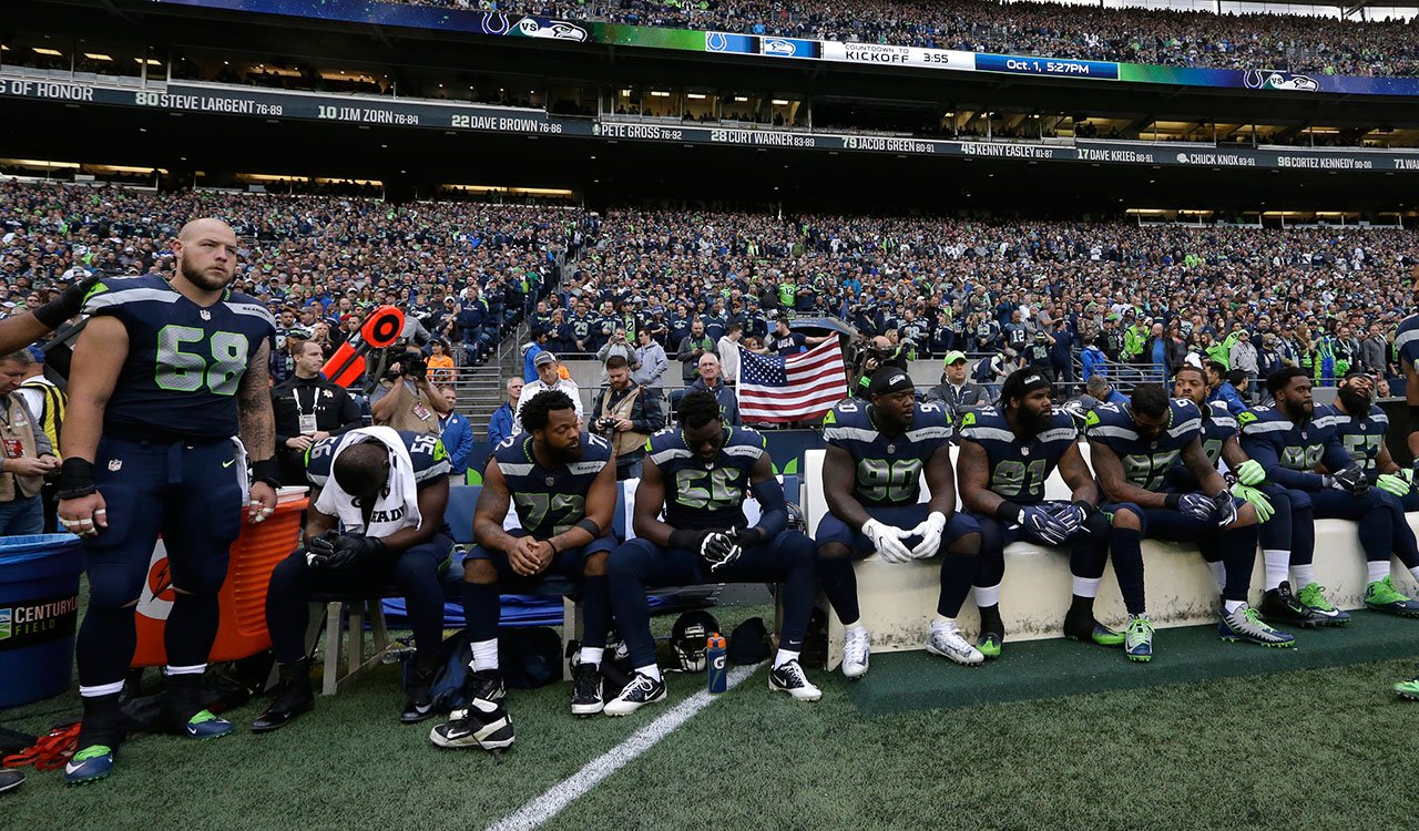 Seattle Seahawks players, including defensive end Michael Bennett, third from left, sit during the singing of the national anthem before an NFL football game against the Indianapolis Colts, Sunday, Oct. 1, 2017, in Seattle. (AP Photo/Elaine Thompson)