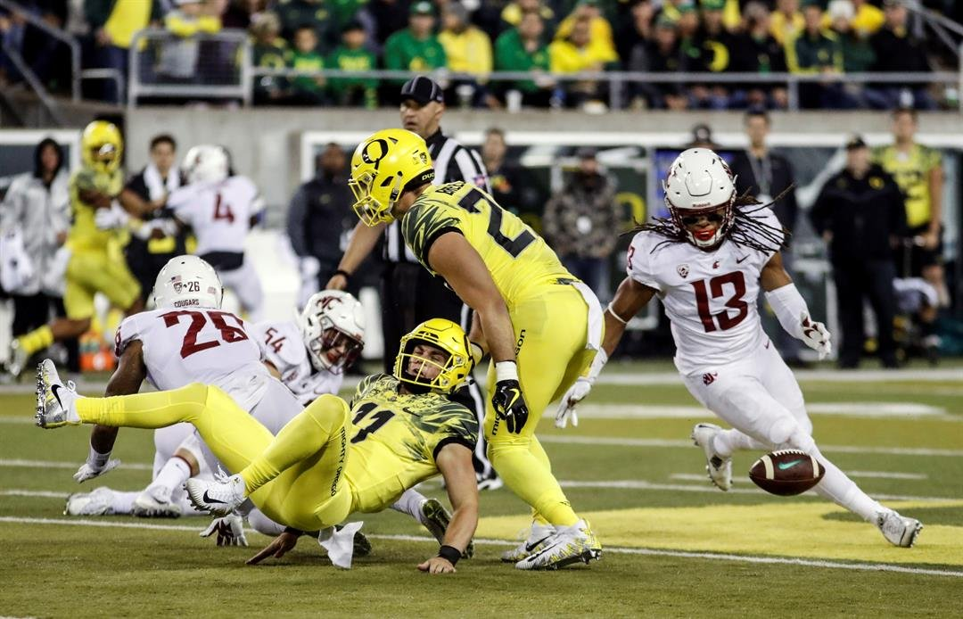 Oregon quarterback Braxton Bermeister fumbles the ball as Washington State linebacker Jahad Woods (13) moves in for the recovery during an NCAA college football game Saturday, Oct. 7, 2017 in Eugene, Ore. (AP Photo/Thomas Boyd)