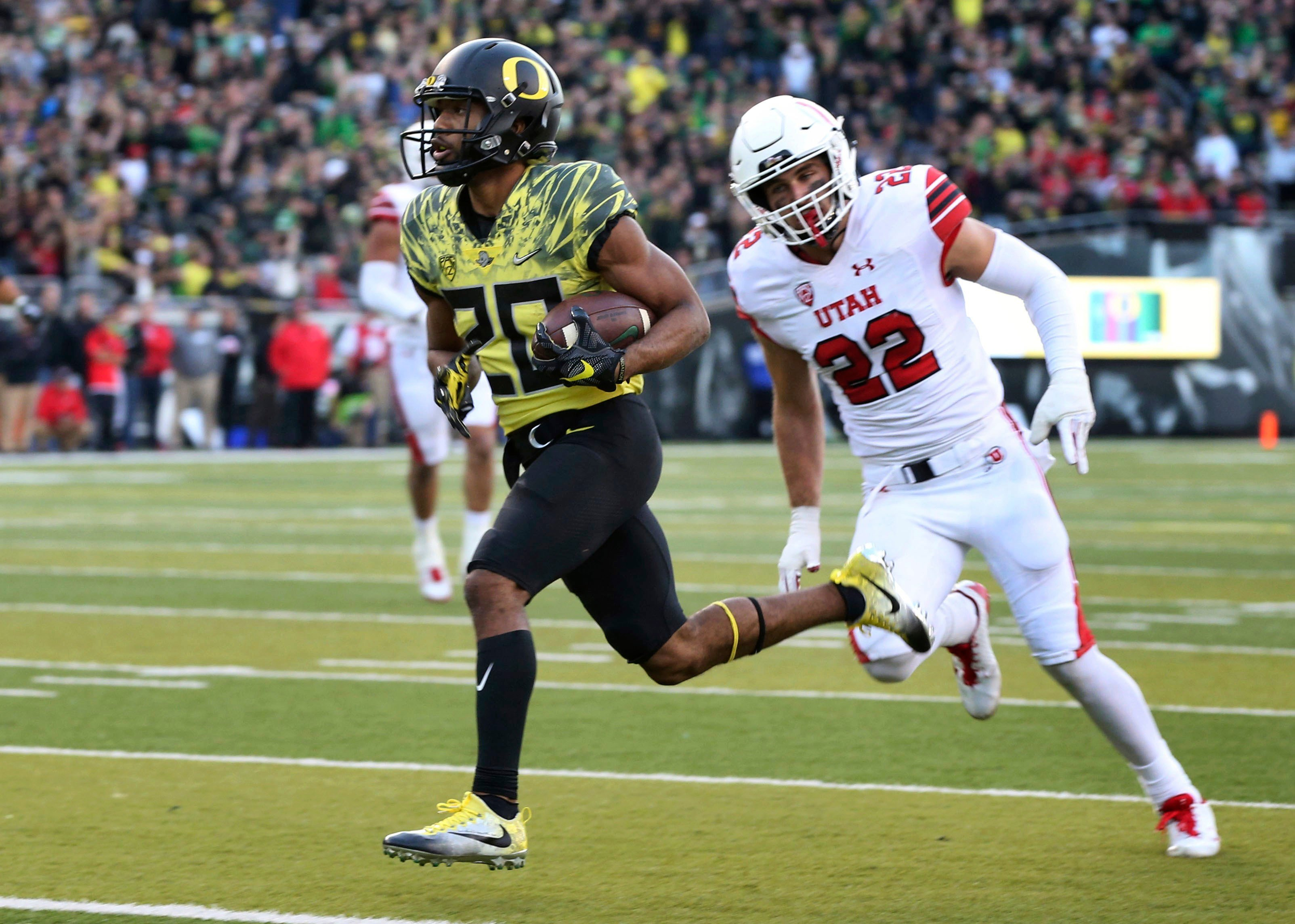 Oregon running back Tony Brooks-James, left, scores a touchdown ahead of Utah's Chase Hansen during the fourth quarter of an NCAA college football game Saturday, Oct. 28, 2017, in Eugene, Ore. (AP Photo/Chris Pietsch)