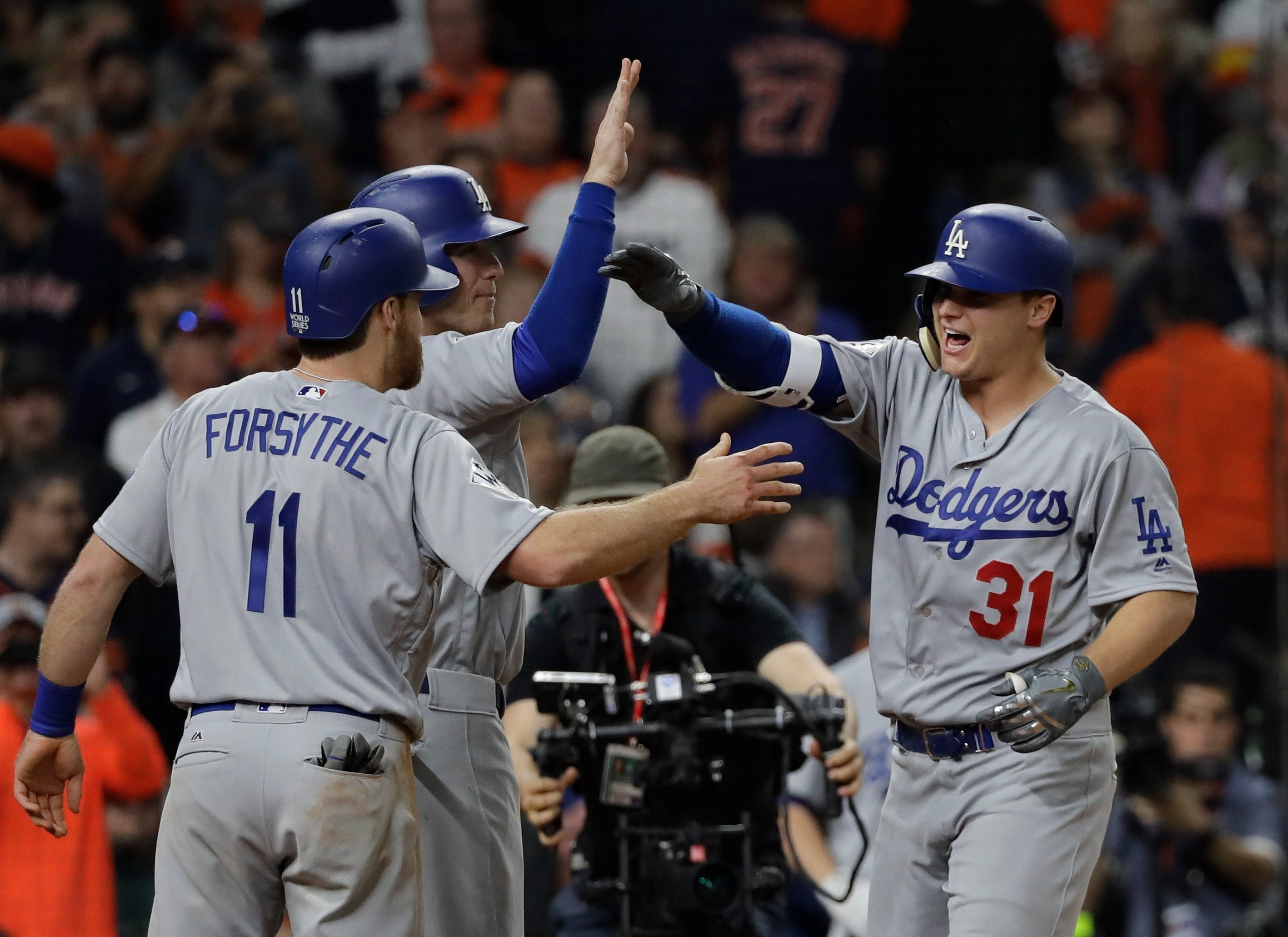 Los Angeles Dodgers' Joc Pederson is congratulated after hitting a three-run home run during the ninth inning of Game 4 of baseball's World Series against the Houston Astros Saturday, Oct. 28, 2017, in Houston. (AP Photo/David J. Phillip)